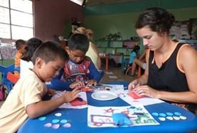 A volunteer sits with children on a Care and Community placement in Ecuador