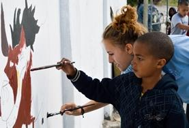 A volunteer paints a mural with a child