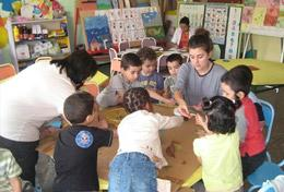 A high school student volunteering in Morocco runs an educational activity with children, under the guidance of a local teacher.