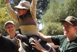 A child reacts during a horse riding session with Equine Therapy volunteers