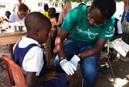 A Public Health Project volunteer works with a child during a public outreach in Ghana