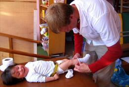 A Medical volunteer dresses a child at a placement in Peru