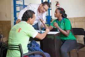 A high school Public Health volunteer holds a baby in the maternity department of a hospital in Jamaica.