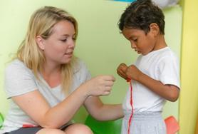 A volunteer interacts with a child on a Social Work placement in Ecuador