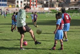 A volunteer plays sport with local children