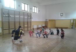 A Football volunteer leads a sports team in Romania through a stretching routine before they start their practice.