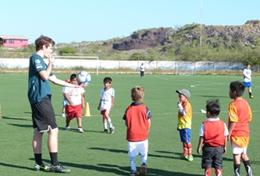 A Multi-sports volunteer prepares to throw a football to a team of children as part of a sports lesson in Ecuador.