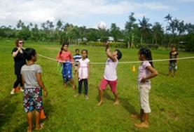 A School Sports volunteer works with a group of school children during a physical education lesson in Samoa.