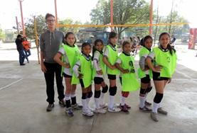 A Volleyball coaching volunteer poses with his team following a training session