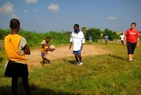 A Sports volunteer works with school children on passing a rugby ball at one of our Rugby placements.