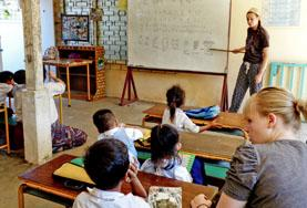 A teaching volunteer demonstrates to a class during a lesson