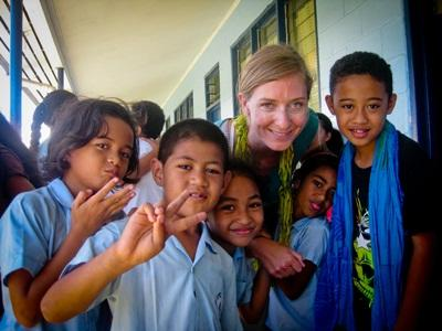 A volunteer poses with her smiling students in Samoa, South Pacific.