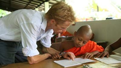 A volunteer helps one of his students in a classroom in Sri Lanka.