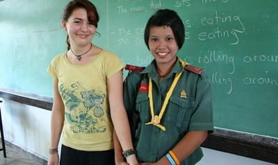 A volunteer stands with her student in Thailand, Asia.