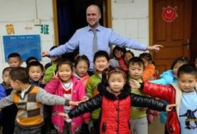 A volunteer poses with children at a Teaching Project placement in China