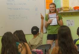 A school child raises his hand to answer a question asked by a Teaching volunteer during an English lesson in Ecuador.
