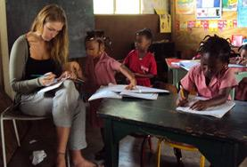 A volunteer works closely with local school children during an English language lesson on our Teaching project in Jamaica.