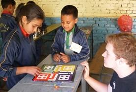 A Teaching volunteer uses a board game to teach school children about colours and numbers at a local school in Nepal.