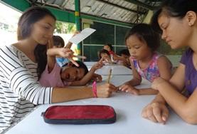A Teaching volunteer works closely with school students during an English language lesson at our placement in the Philippines.