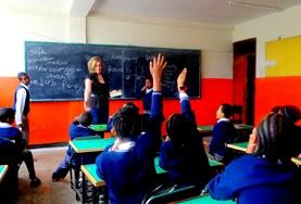 Students raise their hands in a classroom in Ethiopia