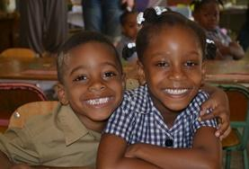 Two children smile for a photo at a French Teaching volunteer placement in Jamaica