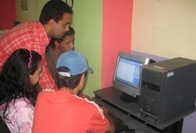 School students and volunteers gather around a computer in preparation for a lesson on our volunteer Teach IT project in Morocco.